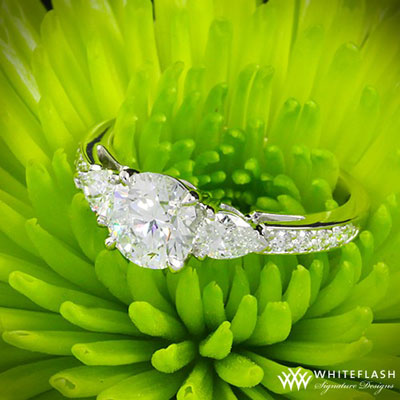 three stone diamond engagement ring on a grass