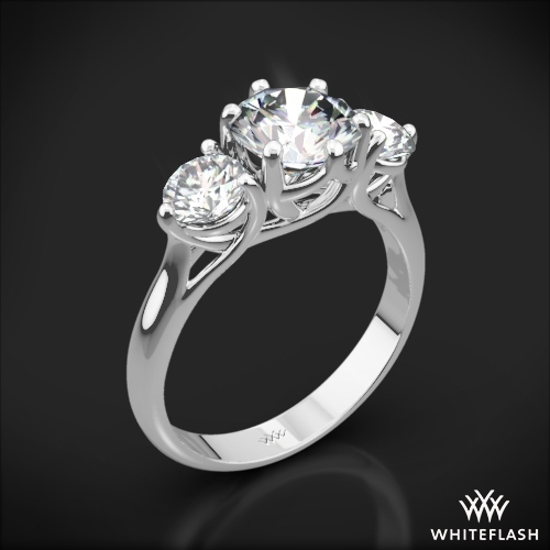 This gorgeous Three Stone Engagement Ring weaves 6 prongs around your center diamond and 3 prongs around two 0.25ct Whiteflash 'A Cut Above' Hearts and Arrows D